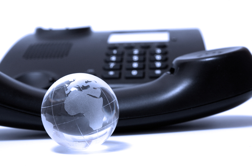 Black business phone and glass globe in blue light
