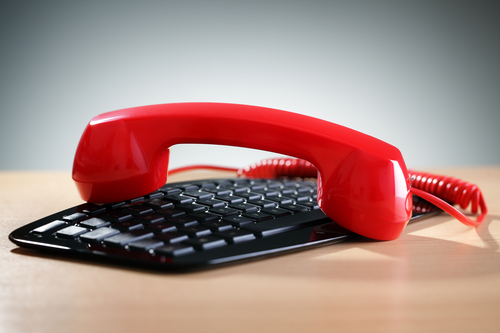 Red telephone receiver on computer keyboard concept for internet phone or voice over ip