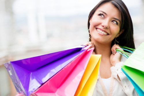Thoughtful woman holding shopping bags and looking up