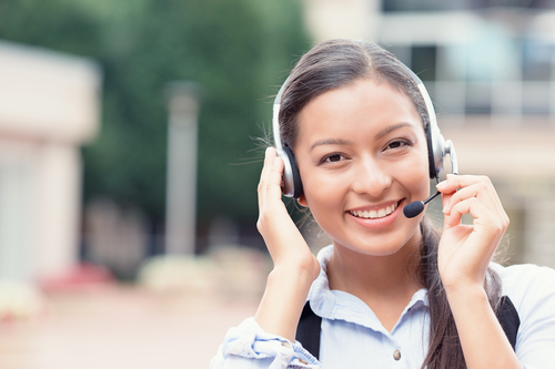 Closeup portrait smiling young female customer service representative call center agent support staff operator with phone headset isolated background with trees city building. Positive face expression