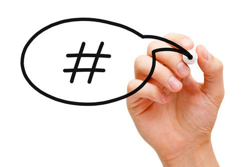 Hand sketching Hashtag Speech Bubble Concept with black marker on transparent wipe board.