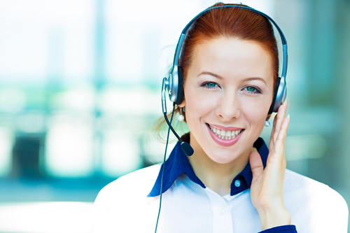 Closeup portrait young happy successful business woman, customer service representative, call centre worker, operator, support staff speaking with head set isolated background corporate office windows